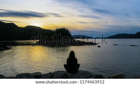 Contemplative woman sitting in a shore in front of the beautiful fjord of Saguenay at Petit-Saguenay Photo stock ©