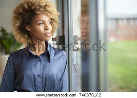Contemplative young afro-american woman looking out the window.