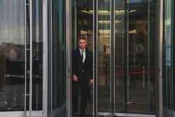 Contemplative young man businessman in style wear clothes and with briefcase leaves business building near corporate company, lifestyle. Male banker going out from office located in financial district