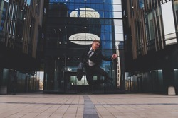 Contemplative young man businessman with briefcase leaves business building near corporate company and jumping jump, lifestyle. Male banker going out from office located in financial district