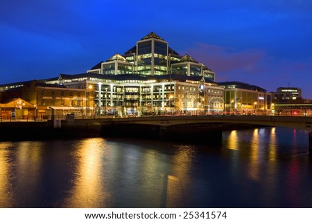 Contemporary architecture of modern office building at night in Dublin downtown, Ireland, reflections on river Liffey waters.