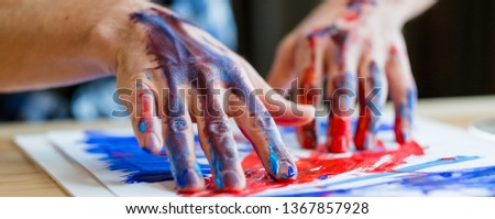 Contemporary art trend. Closeup of male hands creating abstract picture with red and blue acrylic paint on his finger tips.