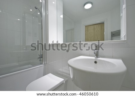 contemporary bathroom with floor to ceiling tiles and white suite - stock photo