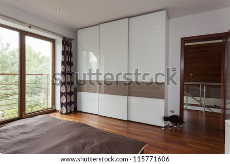 Contemporary bedroom with balcony and huge wardrobe - stock photo