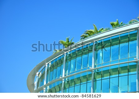 Contemporary building made of glass and iron with palm tree on the roof