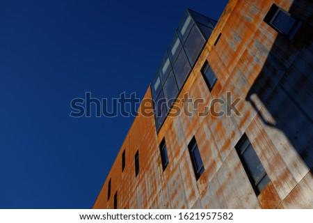 Contemporary corten steel building. Corten weathering steel.  Modern building against blue sky.