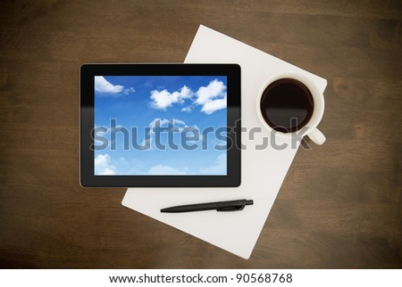 Contemporary digital tablet with cloudy sky on screen lying on worktable with paper, pen and cup of coffee. Concept image on cloud-computing theme. Directly above view.