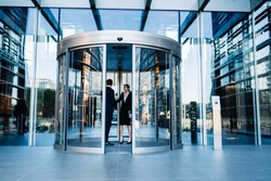 Contemporary diverse formal man and woman standing together inside of round revolving doors of modern glass office building and talking