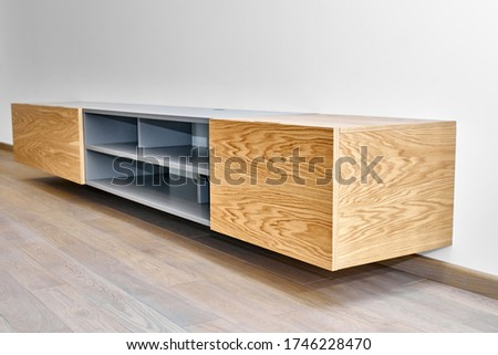 Contemporary floating media cabinet in living room. Wall mounted wooden cabinet ストックフォト ©