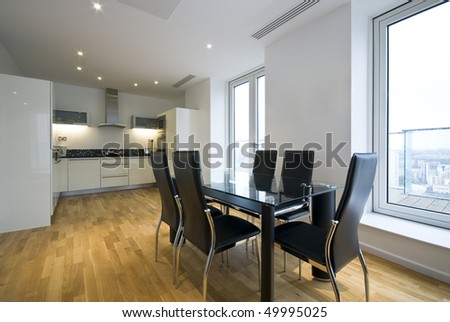 Contemporary fully fitted kitchen in white with dining area and large dining table for six