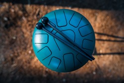 Contemporary green hand pan steel tongue drum musical instrument and a pair of black drum sticks placed on it. Relaxing and healing sounds, music therapy.