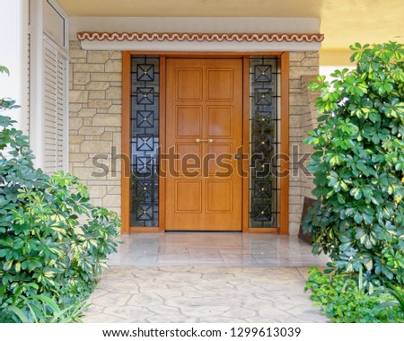 Contemporary house entrance wood and glass door on stone decorated wall, Athens Greece