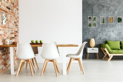 Contemporary interior design of dining space with communal table against brick wall and open living room with simple sofa and plant decorations on textured gray wall