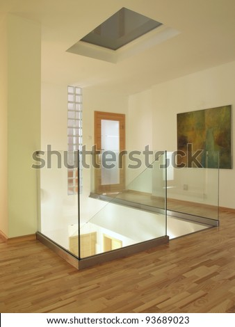 Contemporary interior with wooden floor and glass staircase,