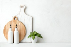 Contemporary kitchen background with kitchen utensils standing on white countertop, blank space for a text, front view