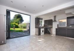 Contemporary Kitchen with bi folding aluminium doors leading to garden decking UK