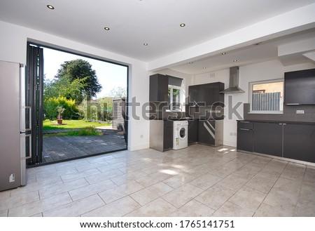 Contemporary Kitchen with bi folding aluminium doors leading to garden decking UK Сток-фото ©