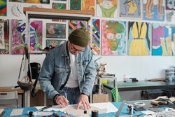 Contemporary leatherworker in denim jacket and jeans bending over table while outlining paper pattern by workplace