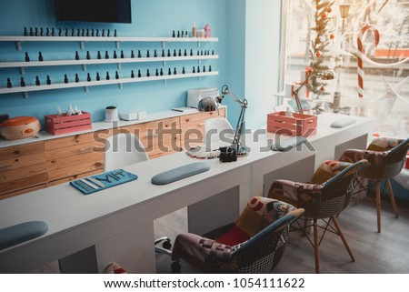 Contemporary manicure tools locating on long desk in beauty salon. Cozy chairs situating near it. Design concept #1054111622
