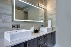 Contemporary master bathroom features a dark vanity cabinet fitted with rectangular his and hers sink and modern wall mount faucets under large mirror. Northwest, USA