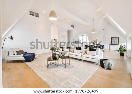 Contemporary minimalist interior design of lounge zone with couches and carpet in attic open space apartment with white walls and loft style Stock photo ©