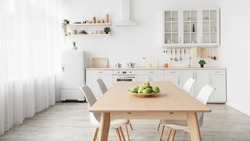 Contemporary minimalist interior of kitchen and dining room. White furniture with utensils and dinner table with chairs in Scandinavian style. Modern light design