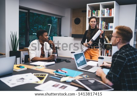 Contemporary multiethnic men and woman communicating while gathering with coffee and gadgets at table in modern stylish office and working in team