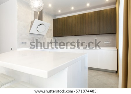 Contemporary open space kitchen in a luxury apartment. White counter with white furniture. #571874485