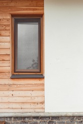 Contemporary private house facade with window, combined design of wood planks and plaster .