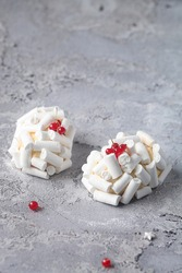 Contemporary Red Fruit and Matcha Tea Individual Mousse Cakes, decorated with Meringue Cookies, on a grey background.