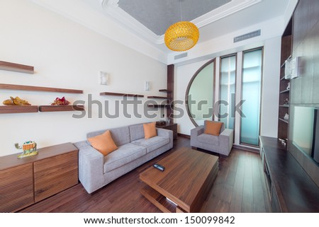 Contemporary room with a sofa, an armchair and a wooden table in the center