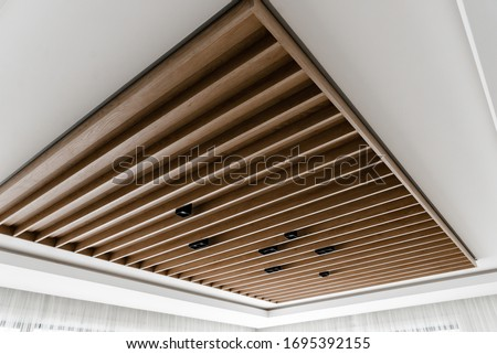 contemporary suspended wood ceiling,loft style ceiling,beautiful wooden ceiling,black light bulbs in a wooden ceiling,concrete wood ceiling,brown beams on the ceiling