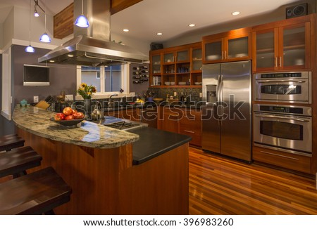 Contemporary upscale home kitchen interior with wood cabinets and floors, granite countertop, accent lighting and stainless steel appliances including double oven, refrigerator and vent hood