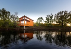Contemporary wooden single family house. Retreat rental. Perfect getaway. Wooden house on a island with oaks. organic architecture. Wooden minimalistic house with big panoramic windows.