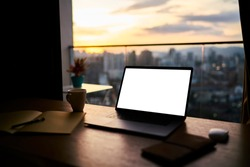 Contemporary workspace with blank screen netbook and planner placed on wooden table near window of skyscraper overlooking downtown during sunset