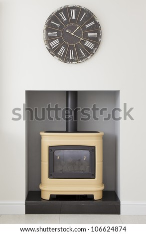 Contemporary yellow wood burning stove with clock in a modern kitchen