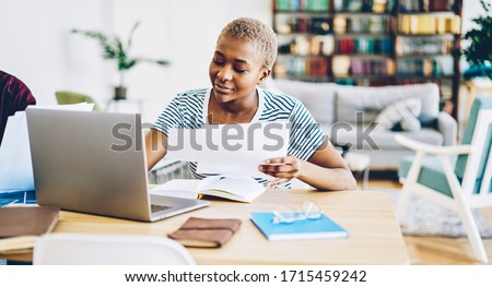 Content African American businesswoman in casual outfit sitting at table with netbook and doing paperwork while working remotely in cozy home office