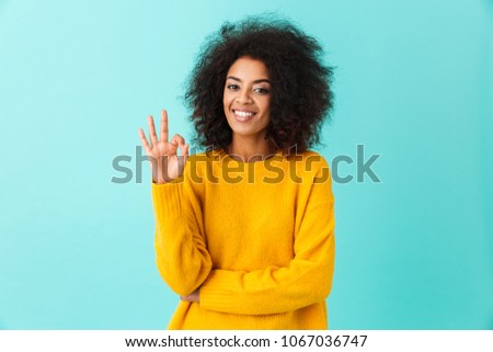Content american woman in colorful shirt smiling on camera and gesturing ok sign isolated over blue background