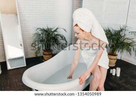 Content attractive young tourist female pampering herself with mineral water procedure in wellbeing area of spa hotel. hydrotherapeutic procedure concept. #1354050989