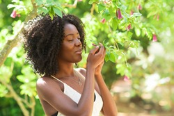 Content Black Woman Smelling Flowers in Park