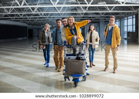 Content company of young people getting ready for travelling. They are carrying cart with baggage through terminal. Girl sitting on bags and exulting