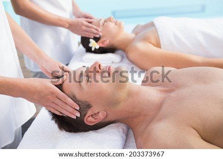 Content couple enjoying head massages poolside outside at the spa #203373967