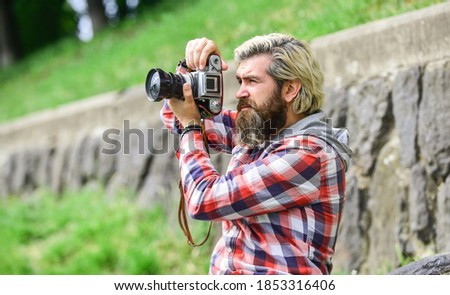 Content creator. Masterpiece shot. Man with beard shooting photos. Photographer concept. Man bearded hipster photographer hold vintage camera. Photographer amateur photographer nature background.