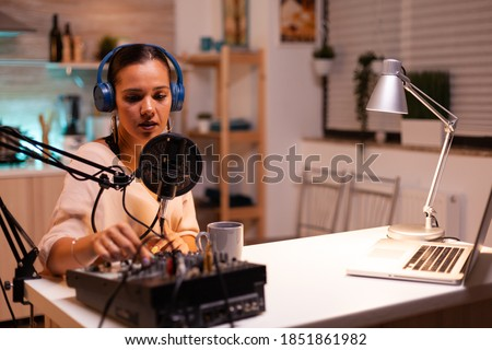 Content creator wearing headphones while recording new episode for podcast. Creative online show presenter On-air online production internet broadcast show host streaming live content, recording media Foto stock ©