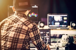 Content creators he is working in studio  and use laptop editing video footage upload to social media