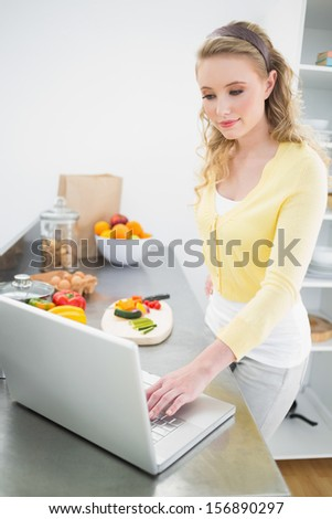 Content cute blonde using laptop in bright kitchen