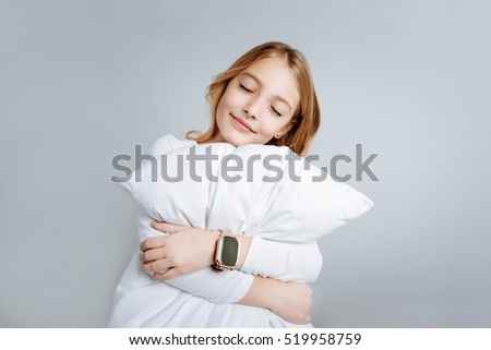 Content cute girl embracing pillow