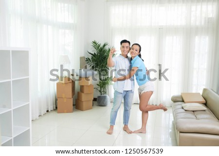 Content embracing Asian couple standing in light room of new modern apartment showing keys #1250567539