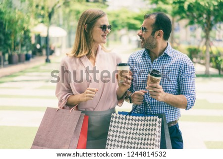 Content family couple walking outdoors after shopping. Handsome man and beautiful woman with paper bags drinking coffee and talking on sidewalk. Weekend and consumerism concept