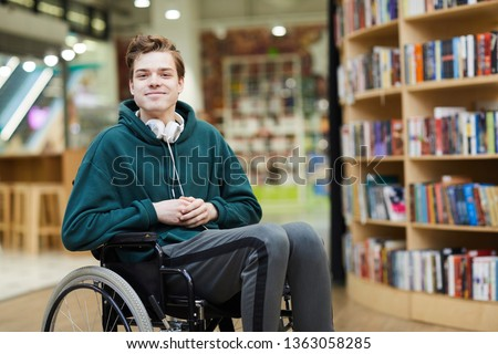 Content handsome young disabled student with headphones on neck siting in wheelchair and looking at camera in modern library or bookstore #1363058285